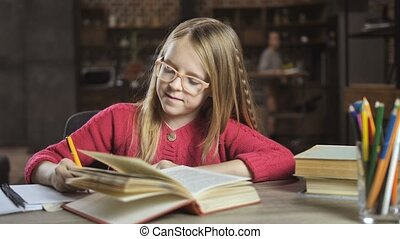 Smiling teenage girl studying lessons at home