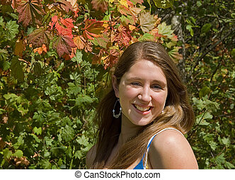 Smiling Teenage Girl With Autumn Leaves