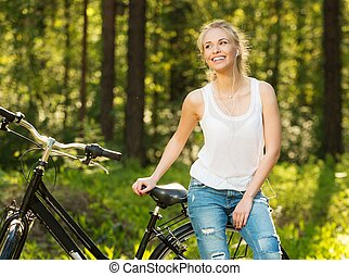 Smiling teenage girl with bicycle in a park on sunny day