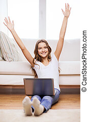 smiling teenage girl with laptop computer at home