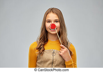 smiling teenage girl with red clown nose