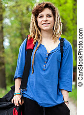 Smiling teenage girl with travel bag outside