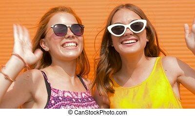 smiling teenage girls in sunglasses waving hands - summer...