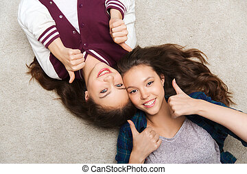 smiling teenage girls on floor showing thumbs up