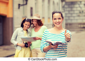 smiling teenage girls with city guide and camera