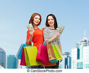 smiling teenage girls with shopping bags and money -...