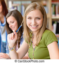 Smiling teenage student girl at study room library high...