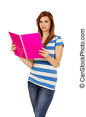 Smiling teenage woman reading her notes
