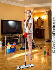 teenager girl cleaning floor at living room with swab - ...