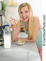 Smiling teenager girl having breakfast eating flakes with...