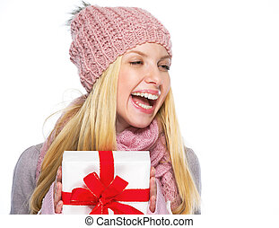Smiling teenager girl in winter hat and scarf with presenting box looking on copy space