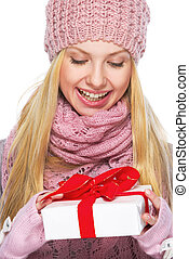 Smiling teenager girl in winter hat and scarf with presenting box