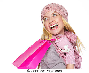 Smiling teenager girl in winter hat and scarf with shopping bag looking on copy space
