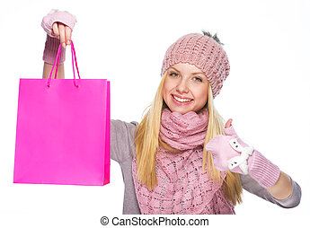 Smiling teenager girl in winter hat and scarf showing shopping bag and thumbs up