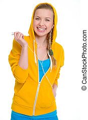 Smiling teenager girl listening music in earphones