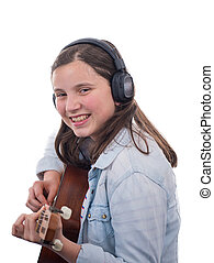 smiling teenager girl playing acoustic guitar on white