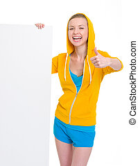 Smiling teenager girl showing blank billboard and thumbs up
