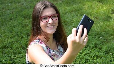 Smiling teenager girl taking selfie with smart phone