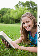Smiling teenager holding a book while lying in a parkland and looking at the camera