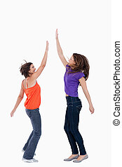 Smiling teenager keeping her hand in the air while her...