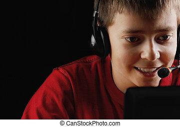 Smiling teenager playing on laptop