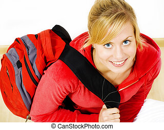 smiling teenager sitting on floor with backpack