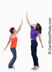 Smiling teenager standing on the tips of her toes while her friend is trying to touch her hand