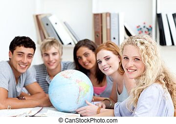 Smiling teenagers in a library working with a terrestrial ...