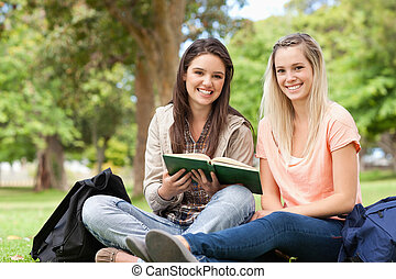 Smiling teenagers sitting while studying with a textbook