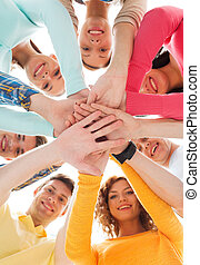 smiling teenagers with hands on top of each other -...