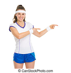 Smiling tennis player pointing on copy space