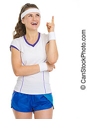 Smiling tennis player pointing up on copy space