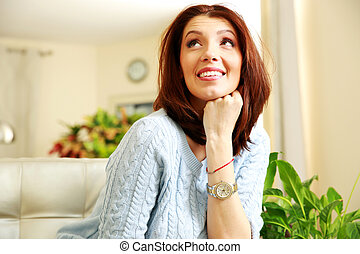 Smiling thoughtful woman looking up at home