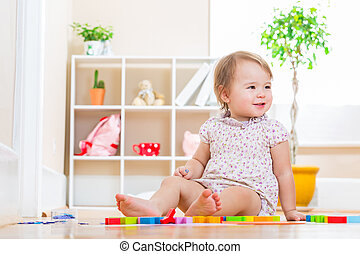 Smiling toddler girl playing with her toy blocks
