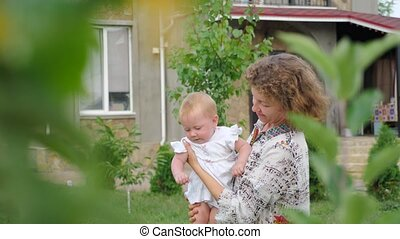 Smiling toddler with mother. Life beginning concept. Business lady with a child. Baby girl on mother's hands.
