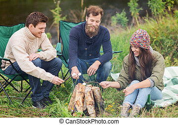 smiling tourists cooking marshmallow in camping - adventure,...