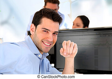 Smiling trader in front of desktop computer