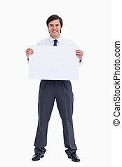 Smiling tradesman holding blank sign