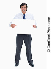 Smiling tradesman pointing at blank sign in his hands