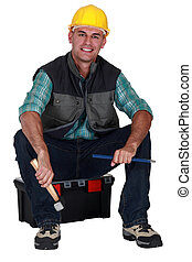 Smiling tradesman sitting on his toolbox and holding tools