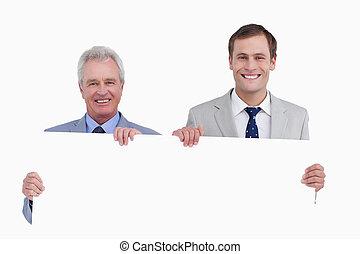 Smiling tradesmen holding blank sign
