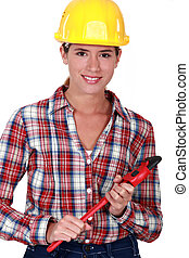 Smiling tradeswoman holding a pipe wrench