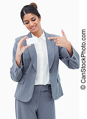 Smiling tradeswoman pointing at blank business card