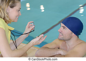 smiling trainer showing stopwatch at swimmer at the leisure center