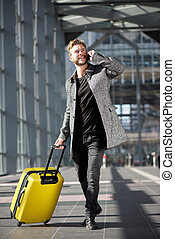 Smiling travel man walking with cell phone and suitcase