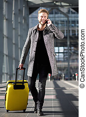 Smiling travel man walking with mobile phone and suitcase