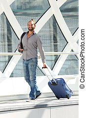Smiling travel man walking with suitcase and smart phone