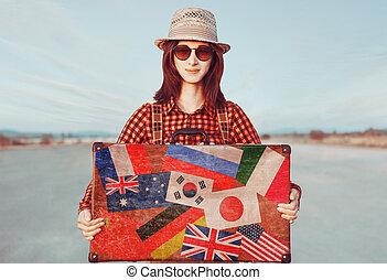 Smiling traveler woman holding suitcase