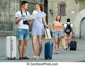 smiling travelers holding map in hands and looking for their way in european town
