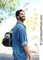 Smiling traveling man with bag on the street